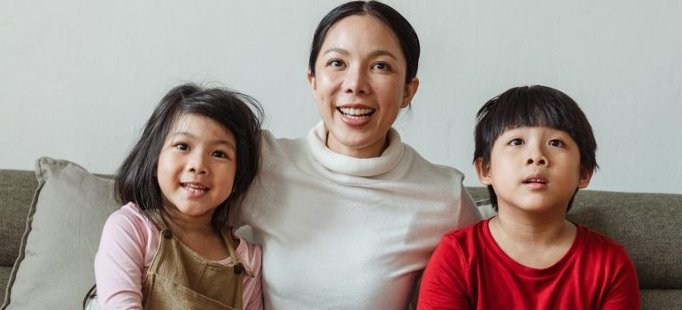 woman with two kids watching tv