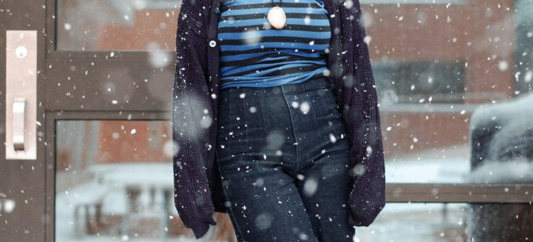 a woman standing on snowy street and thinking about the cheapest time to relocate in CA