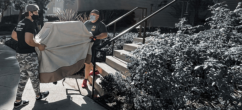 movers carrying kitchen appliances