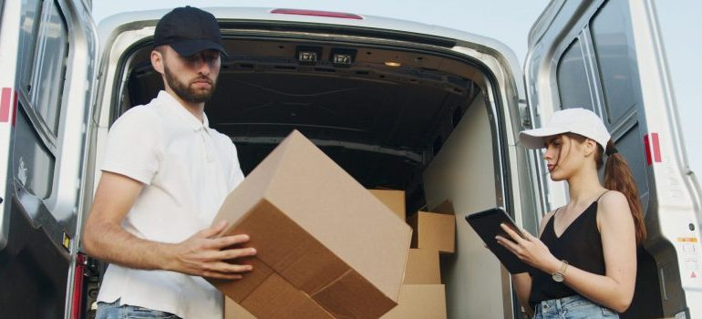 two people loading a moving van with cardboard boxes