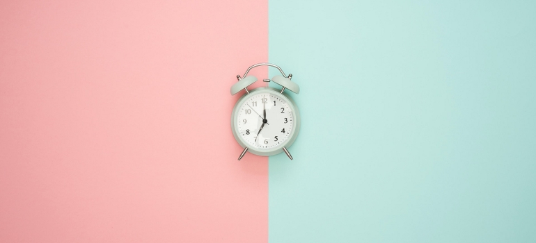 a clock on a pink and teal background