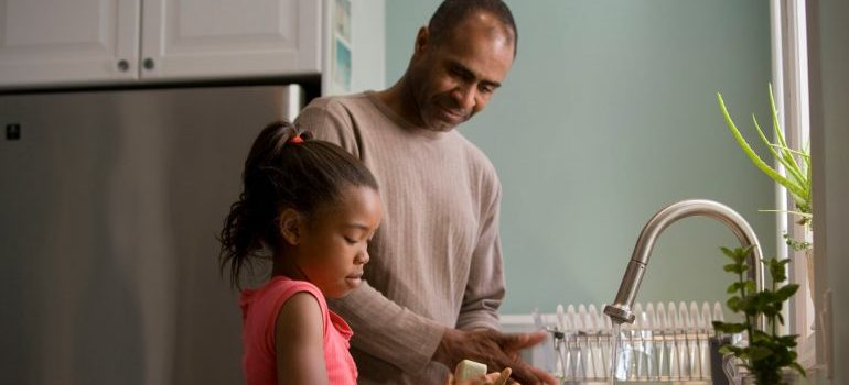 A father and daughter washing dishes together