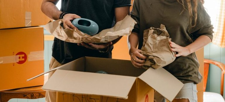 a couple using packing paper, preparing items for the relocation