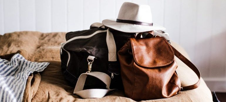 A bag and a backpack with the necessary things on the bed