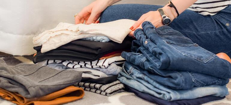 folding clothes to pack in your essentials bag for a long distance move from CA to NY