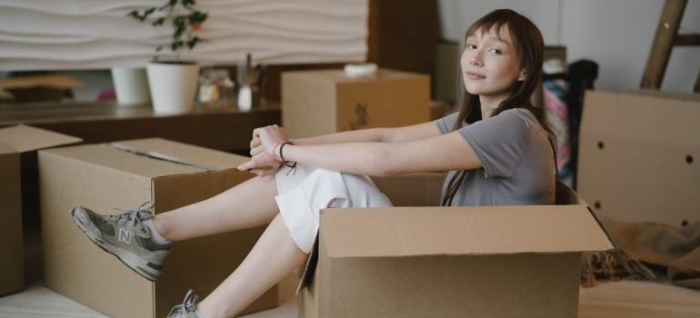 A woman sitting in a moving box