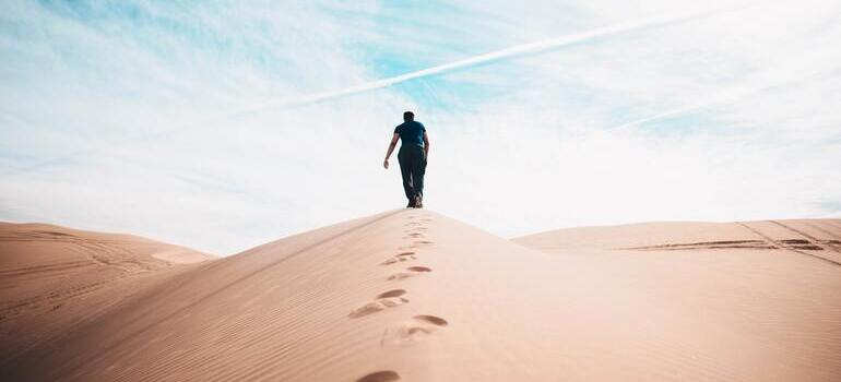 person walking on the sand