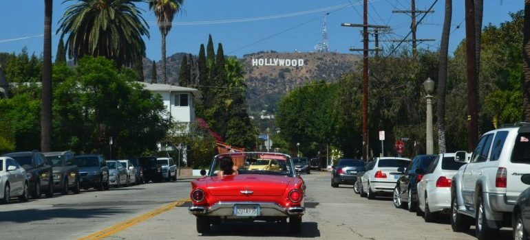 Person in red car driving to one of the places to see after moving to LA